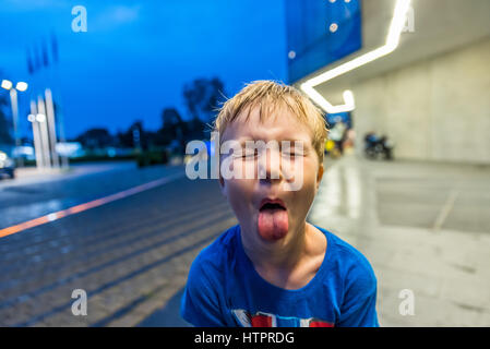 Little boy showing his tongue with fascial expression. - Stock Photo