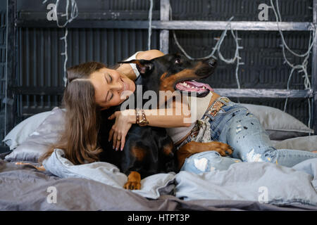 Young pretty woman with black doberman dog in the bed - Stock Photo