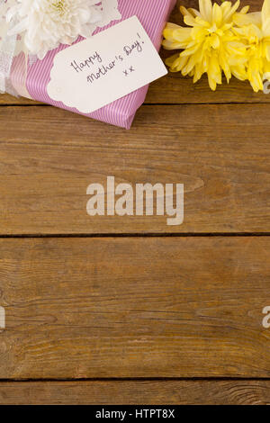 Happy mothers day card on gift box with flowers on table - Stock Photo