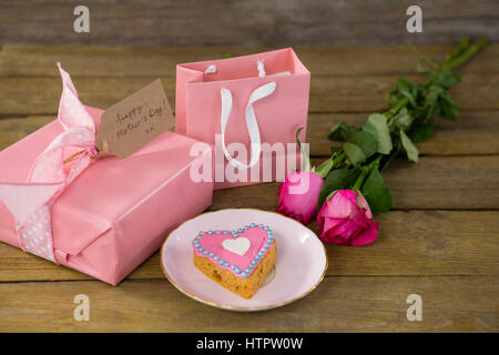 Gift box with roses and heart shape cookies on wooden plank - Stock Photo