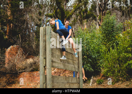 Female trainer assisting woman to climb a wooden wall during obstacle course - Stock Photo