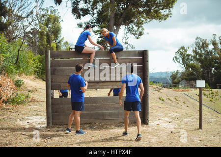 Female trainer assisting fit woman to climb over wooden wall during obstacle course in bootcamp - Stock Photo