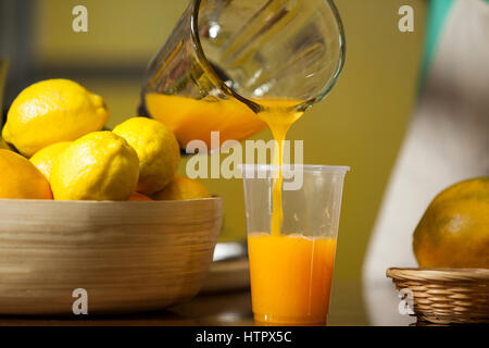 Female staff pouring juice into glass at counter in health grocery shop - Stock Photo
