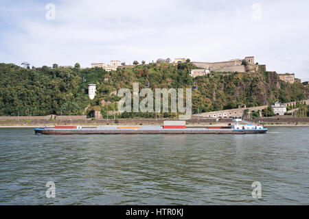 inland container vessel passing fortress Ehrenbreitstein in Koblenz/ Germany - Stock Photo