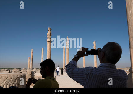 Tourists capture images on their phones and cameras at the ancient city of Persepolis, Fans Province, Iran - Stock Photo