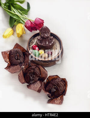 Easter composition of chicken made of chocolate, sitting in a nest, painted eggs and chocolate cupcakes on a white - Stock Photo