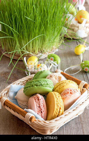 multicolored meringues macaroons in a wicker basket Easter eggs - Stock Photo