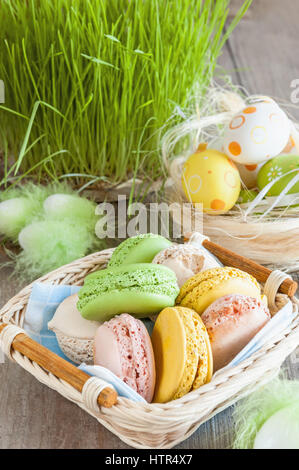 multicolored meringues macaroons in a wicker basket of Easter eggs on a grass background for Easter - Stock Photo