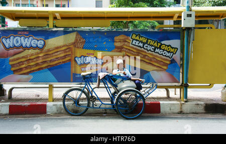 Ho Chi Minh city, Viet Nam, Asian man relax on pedicab at bus station, Vietnamese male earn money by cyclo driver, - Stock Photo