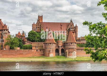Castle of the Teutonic Order in Malbork, Poland on the river Nogat. The castle complex is the largest brick building - Stock Photo