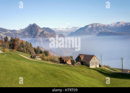 The Swiss Alps and lake Lucerne with a farmhouse and grassy hillside on a misty autumn day in Honegg, Switzerland - Stock Photo