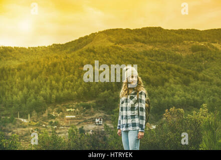 Young woman traveler in chekered shirt hiking in the mountains - Stock Photo