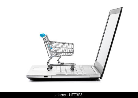 internet store concept - shopping cart on laptop keyboard - Stock Photo