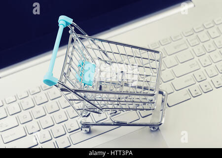 internet shopping concept - cart on computer keyboard - Stock Photo