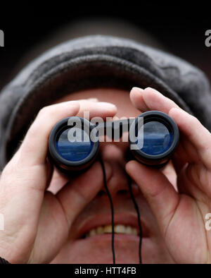 A racegoer watches The Sky Bet Supreme Novices' Hurdle Race run during Champion Day of the 2017 Cheltenham Festival - Stock Photo