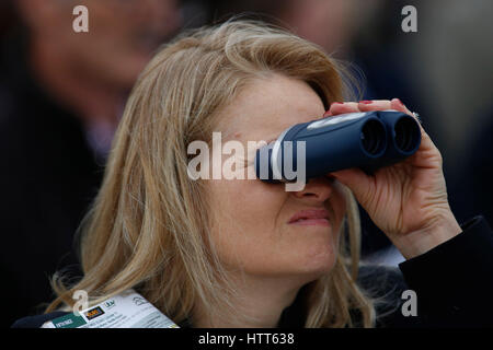 A racegoer watches The OLBG Mares' Hurdle Race run during Champion Day of the 2017 Cheltenham Festival at Cheltenham - Stock Photo