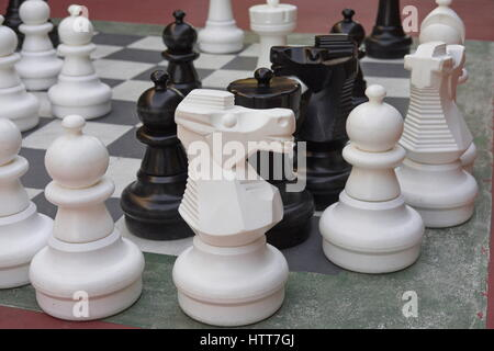 Large black and white chess pieces on a stone board. - Stock Photo