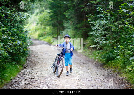 Small boy in helmet walking with bicycle on mountain trail - Stock Photo