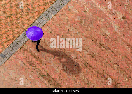Anonymous man in black suit is walking on red and brown tiles square in Italy, hiding from the Sun with a purple - Stock Photo