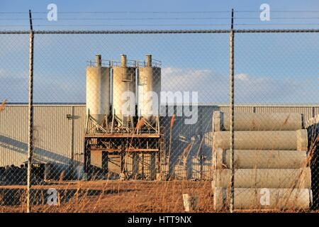 A manufacturing business secured behind a chain link fence, topped by barb wire in this industrial setting in Bartlett, - Stock Photo