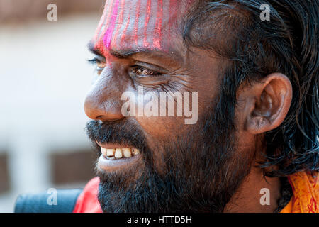 Goa, India - January 2008 - Smiling portrait of an Indian sadhu, holy man, with traditional painted face - Stock Photo