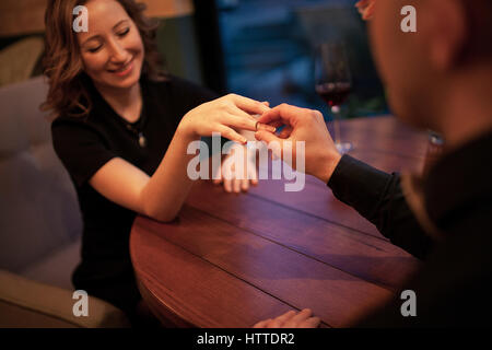Young man makes woman marriage proposal and puts an engagement ring on her finger. They are sitting at table next - Stock Photo