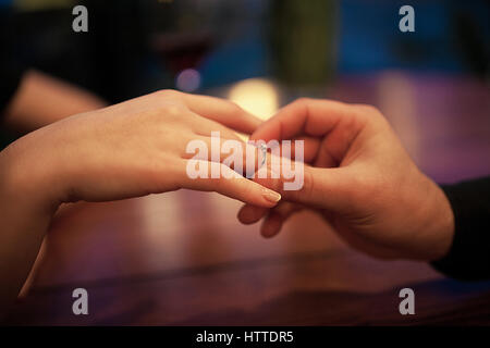 Young man makes woman marriage proposal and puts an engagement ring on her finger. Close up. They are sitting at - Stock Photo