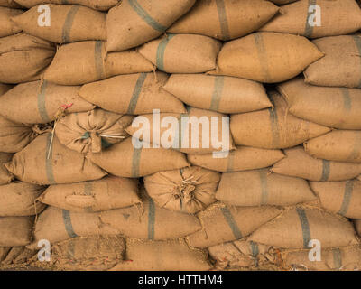 Old hemp sacks containing rice placed stacked in a row. - Stock Photo