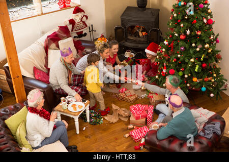 A family are sat around a christmas tree, opening presents and pulling crackers. - Stock Photo