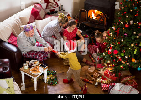 Family at Christmas. They are opening presents and pulling crackers. - Stock Photo