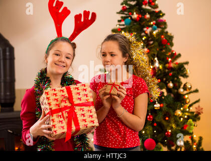 Two sisters posing at Christmas. One is holding a large present and the other is looking at her with a jealous face - Stock Photo