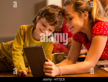 Brother and sister watching something on a digital tablet together. They are lying on the floor at home. - Stock Photo