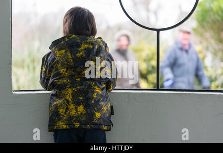 Inside looking out. Child looking out from a shelter to people walking past. - Stock Photo