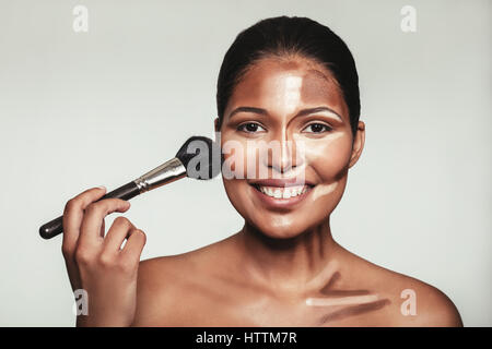 Close up portrait of contour and highlight makeup on female model. Woman applying makeup on her face with brush. - Stock Photo