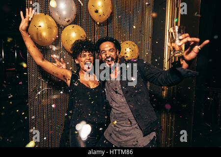 Shot of energetic couple dancing in the night club. Young man and woman having fun at pub party. - Stock Photo