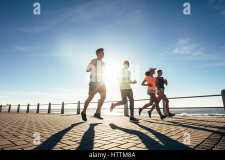 Young people running along a seaside promenade. Runners training outdoors by the seaside on a sunny day. - Stock Photo