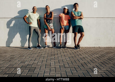 Full length shot of young friends posing together. Group of fitness people standing by a wall outdoors. - Stock Photo