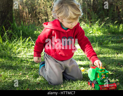 Photo of young boy playing outdoors on grass with harvester toy - Stock Photo