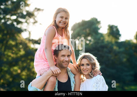Portrait of a mother and smiling father carrying his young daughter on his shoulders while enjoying a day in a park - Stock Photo