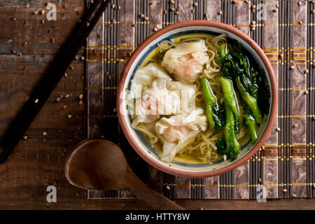 high-angle shot of a earthenware bowl with shrimp wonton noodle soup with choy sum, on a table set for lunch or - Stock Photo