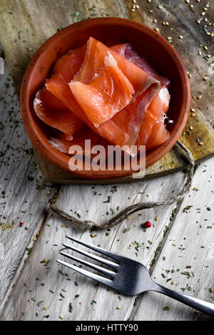 high-angle shot of an earthenware bowl with some slices of smoked salmon, on a rustic wooden table - Stock Photo