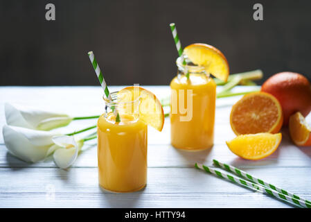 Fresh orange juice in the jar with straw and calla on white wood table. Vertical shot - Stock Photo