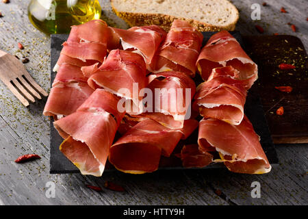 high-angle shot of some slices of spanish serrano ham on a wooden chopping board, and some slices of bread and a - Stock Photo