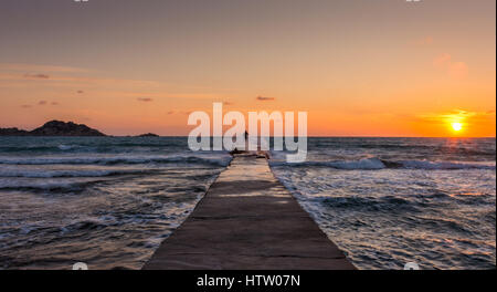 Lone man standing at the end of the pier with waves crashing onto him at sunset. Corfu Greece - Stock Photo