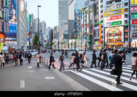 TOKYO, JAPAN - CIRCA APR, 2013: Pedestrian crossroad with walking Japanese people is on Shinjuku district at evening. - Stock Photo