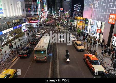 TOKYO, JAPAN - CIRCA APR, 2013: Crossroad with vehicles is in downtown. Illuminated advertising banners are on building - Stock Photo