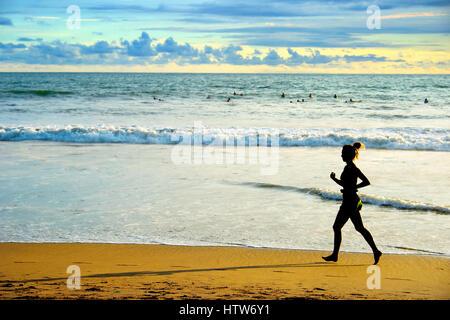Woman running on the beach at sunset. Bali island, Indonesia - Stock Photo