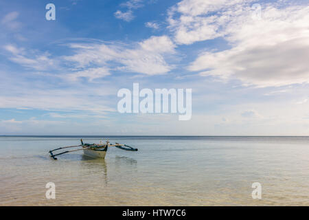 Traditional Filipino fishing boat with seagulls on the outriggers floating in a calm sea. - Stock Photo