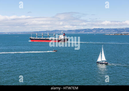 A massive freighter and small sailboat in the bay of San Francisco - Stock Photo