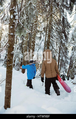 Couple with ski and snowboard walking on snowy mountain - Stock Photo